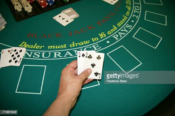 A person holding a pair of cards at a blackjack table
