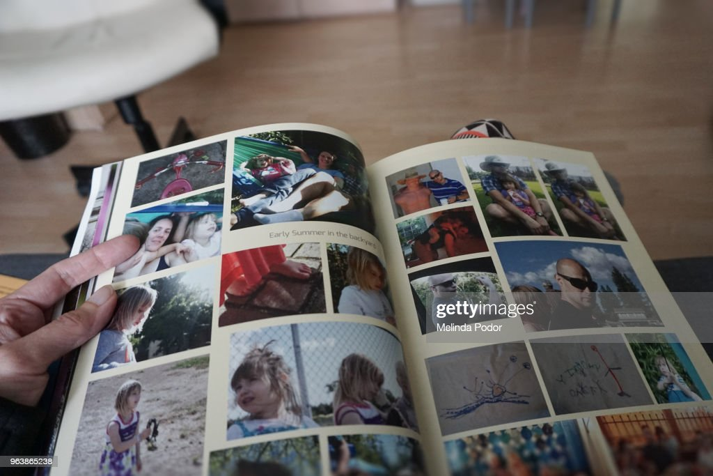 Person holding a photo album created and printed with online software : Stock Photo
