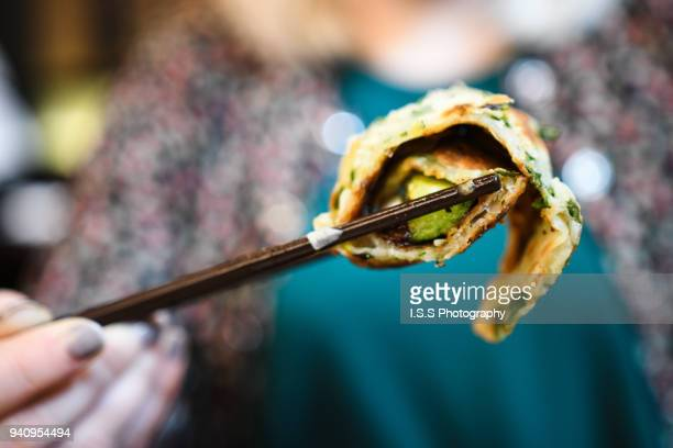 Person holding a piece of Taiwanese beef stuffed scallion pancake 牛肉捲餅 with chopsticks in a restaurant in Taipei