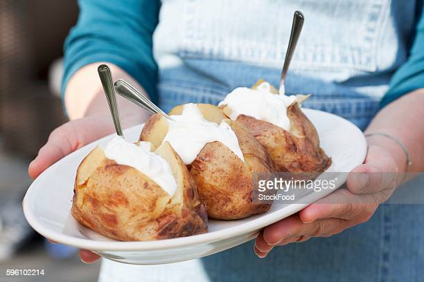 A person holding a plate of jacket potatoes with sour cream