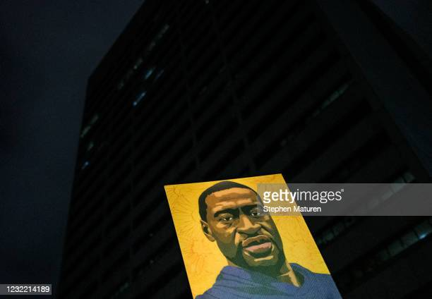 Person holding a portrait of George Floyd marches by the Hennepin County Government Center on April 9, 2021 in Minneapolis, Minnesota. People...