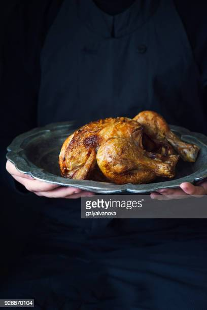 Person holding a Roast chicken on a pewter plate