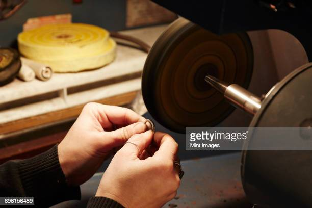 A person holding a small ring and using a grinding machine to shape and polish it. Workbench in a jewellers.