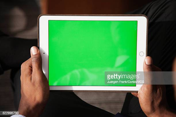 Person holding a tablet showing a green screen