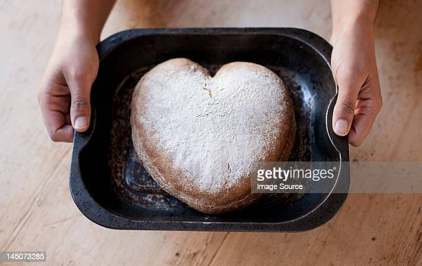 Person holding a tray with heart shaped cake