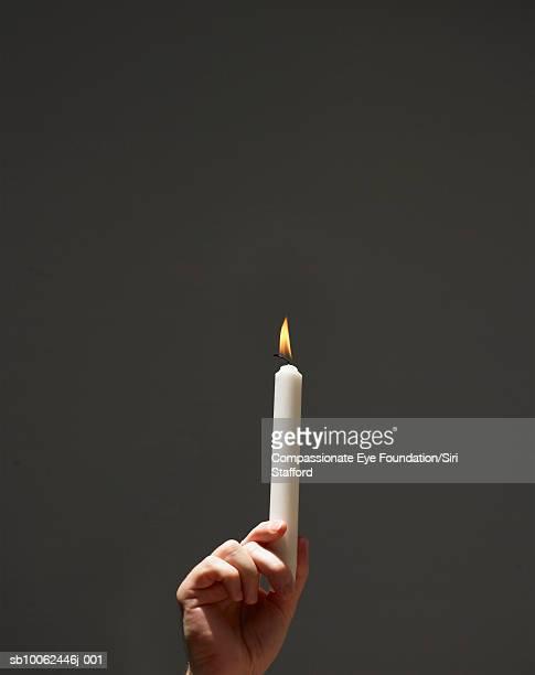"person holding aloft burning candle, close-up of hand - ""compassionate eye"" fotografías e imágenes de stock"