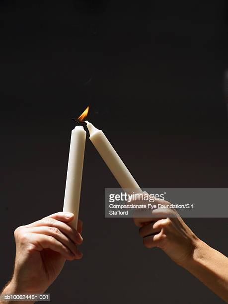 person holding aloft burning candle, trying to light another one, close-up of hands - candela attrezzatura per illuminazione foto e immagini stock