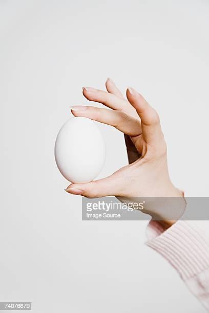 Person holding ein Ei