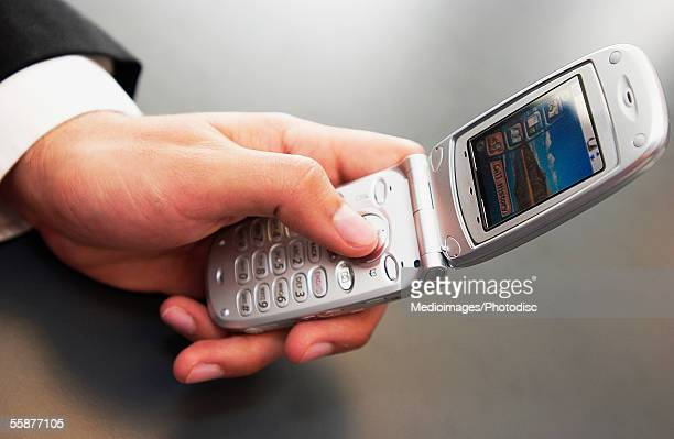 Person holding and dialing cell phone