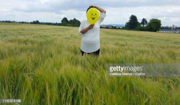 person holding balloon with smiley over face while standing on field - scarecrow faces stock photos and pictures