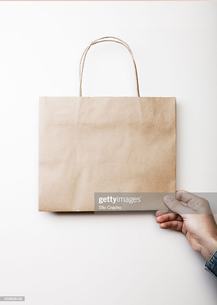 Person holding blank paper bag on white background : Foto stock