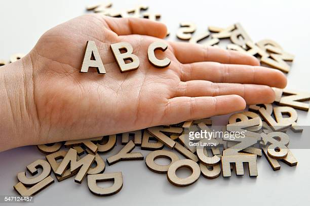 Person holding block letters A,B,C