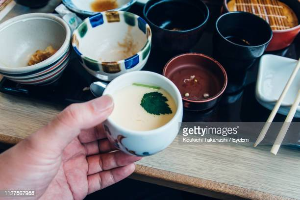 Person Holding Bowl At Table