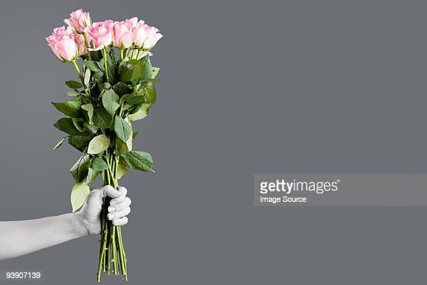 Persona retención ramo de rosas.