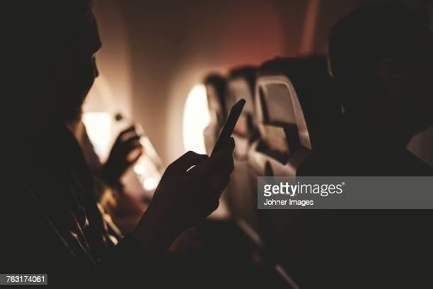 Person holding cell phone in plane