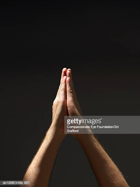 """person holding clasped hands up in air, close-up - """"compassionate eye"""" fotografías e imágenes de stock"""