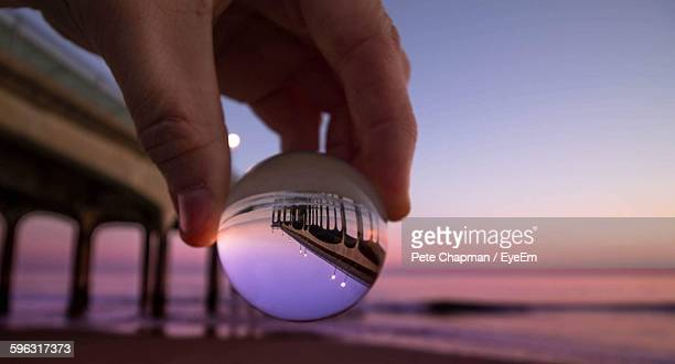 Person Holding Crystal Lens With Reflection Of Bridge