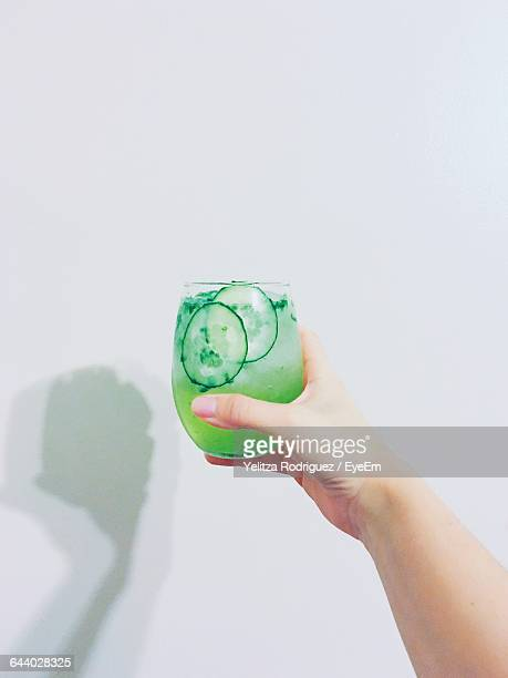 Person Holding Cucumber Juice In Hand