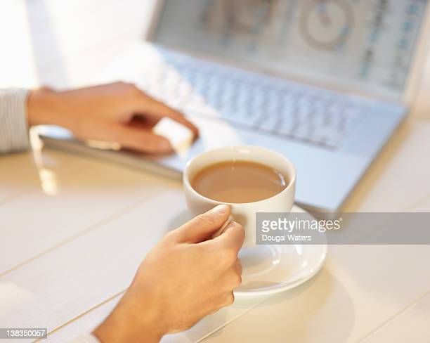 Person holding cup of tea and using laptop.