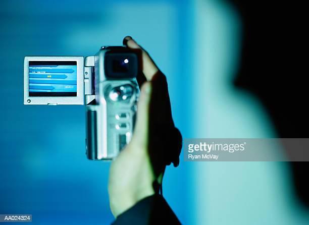 Person holding digital video camera, close-up (blue tone)