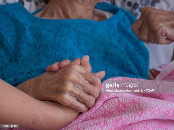 Person holding elderly's hand