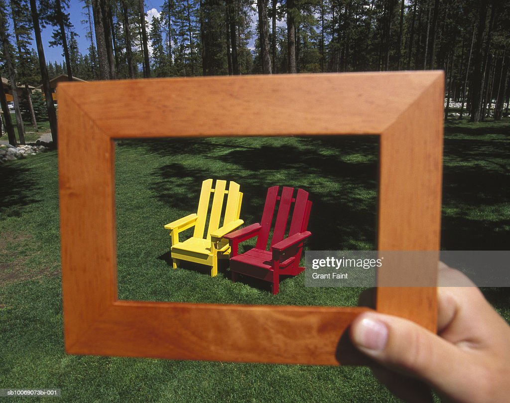Person holding empty frame with deck chairs in center : Stockfoto