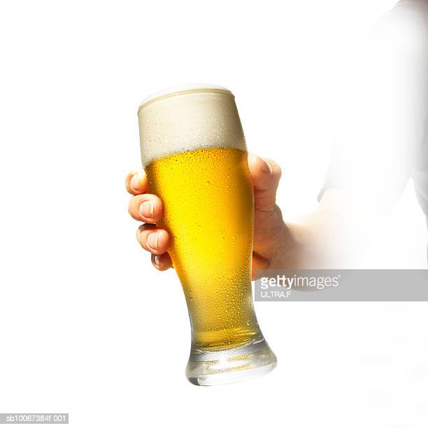 Person holding glass of beer on white background, close-up of hand