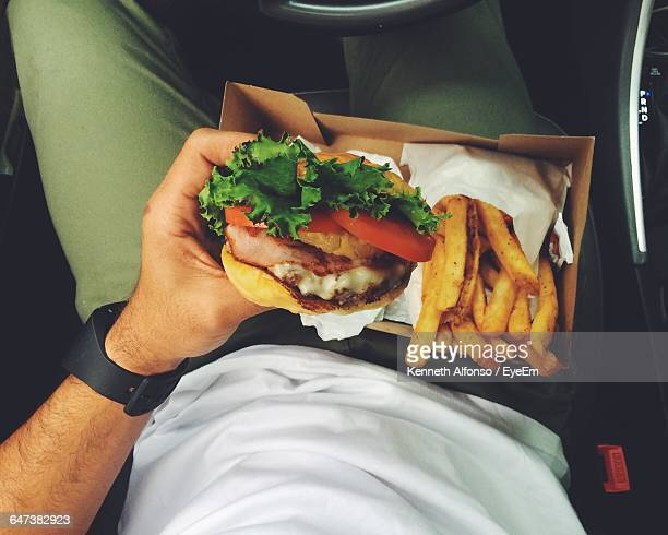 Person Holding Hamburger To Eat Along With French Fries