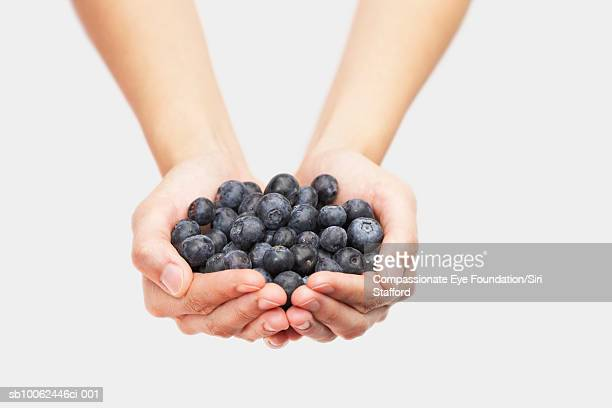 Person holding handful of blueberries, close-up of hands