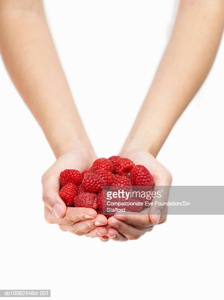 Person holding handful of raspberries, close-up of hands