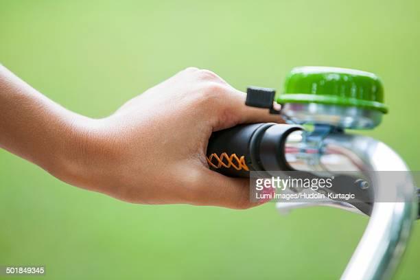 Person holding handlebar of bicycle, close-up, Osijek, Croatia