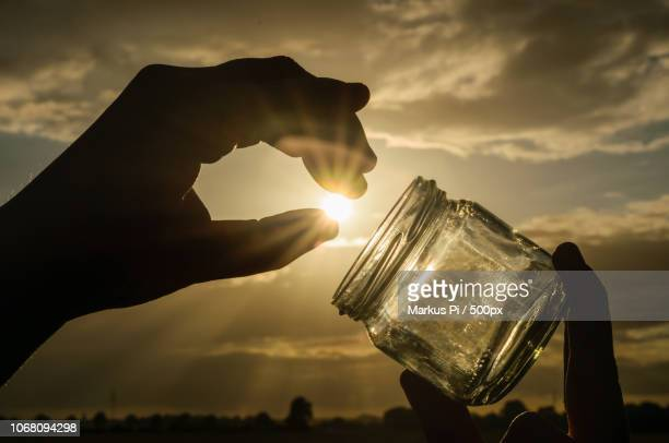 person holding jar against sunny sky - optical illusion stock pictures, royalty-free photos & images