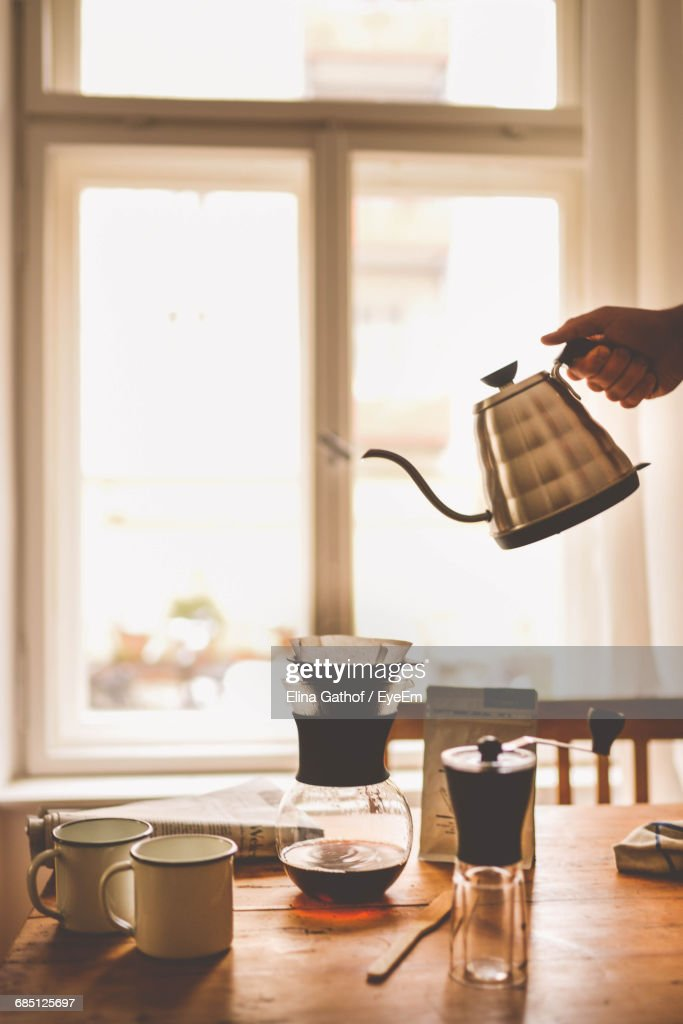 Person Holding Kittle Over Dining Table Next To Stock Photo