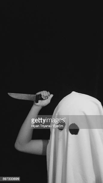 person holding knife with halloween mask against black background - black mask disguise stock pictures, royalty-free photos & images