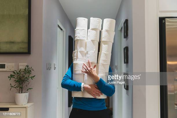 person holding large piles of toilet rolls - social distancing stock-fotos und bilder