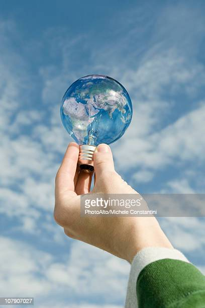 Person holding light bulb in front of sky