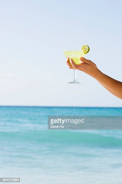 person holding margarita on beach - margarita beach stock photos and pictures