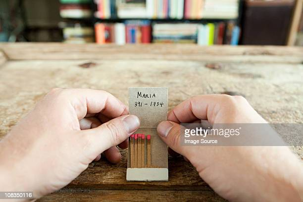 Person holding matchbook with phone number written on it