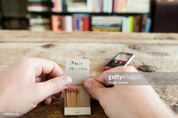 person holding matchbook with phone number written on it - telephone number stock pictures, royalty-free photos & images