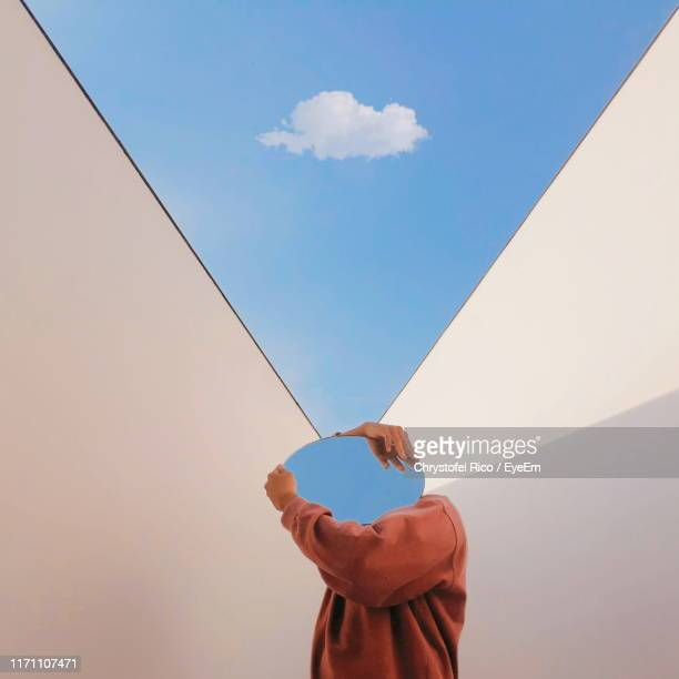 person holding mirror against sky - mirror stock pictures, royalty-free photos & images