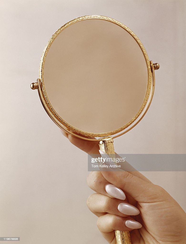 Person holding mirror, close up : Stock Photo