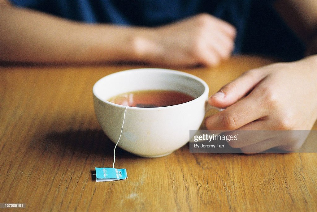 Person holding morning tea cup : Stock Photo