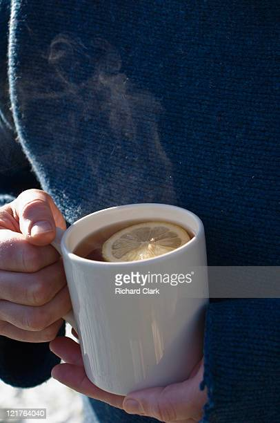 Person holding mug of steaming tea