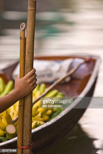 Person holding onto bamboo poles at floating market