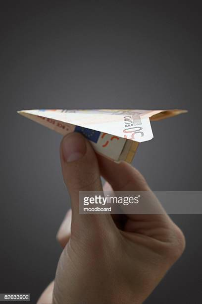 person holding paper airplane made of 50 euro note, close-up of hand - billet de 50 euros photos et images de collection