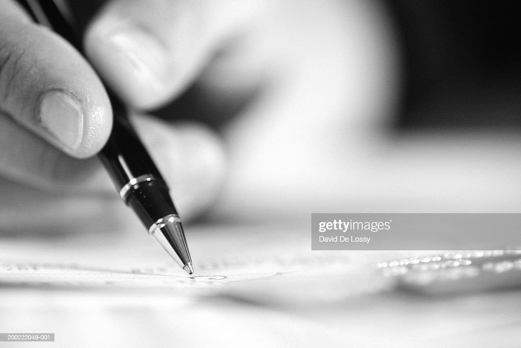 Person holding pen, close-up of hand and object, (B&W) : Stock Photo