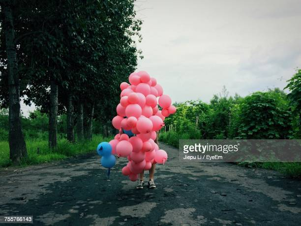 Person Holding Pink Balloons
