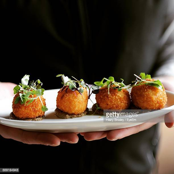 Person Holding Plate With Cheese Ball