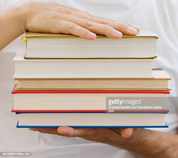 "person holding stack of books, close-up, mid section - ""compassionate eye"" bildbanksfoton och bilder"