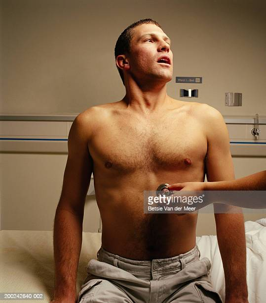 person holding stethoscope to young man's bare chest - chest barechested bare chested foto e immagini stock